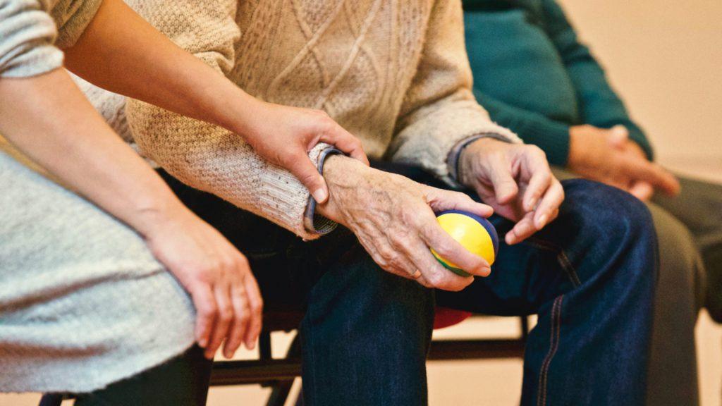 äldre person som sitter med en boll i handen.